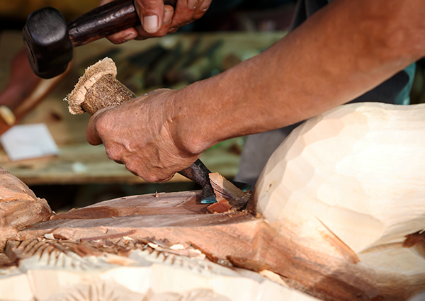 職人が木材を削る